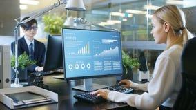 W Biurowym bizneswomanie przy Jej biurkiem, Używa ogłoszenie towarzyskie Co zdjęcie stock