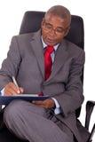 W biurowym krześle biznesmena afrykański obsiadanie Zdjęcia Stock