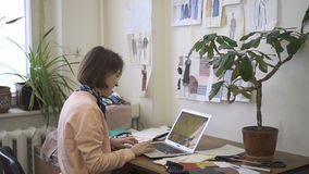 W biurze żeński projektant mody pracuje na laptopie zdjęcie wideo