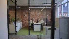 W biurze z szklanymi rozdziałami młoda kobieta pracuje przy komputerem zbiory wideo