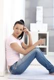 W cajgach przypadkowa dziewczyna i na podłoga koszulki obsiadanie Zdjęcie Stock