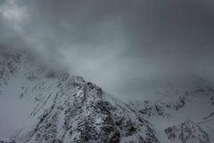 W chmurach śnieżne góry fotografia stock