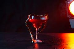 W the ciemny pokój przeciw the tło czerwony jaskrawy lampa szkło z czerwony ciecz i wąż kto przekręcać ono z siebie zdjęcie stock