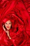 W czerwonej atłasowej tkaninie zmysłowa twarz Obraz Royalty Free