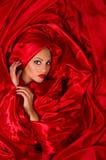 W czerwonej atłasowej tkaninie zmysłowa twarz Zdjęcie Royalty Free