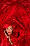 W czerwonej atłasowej tkaninie zmysłowa twarz Fotografia Royalty Free