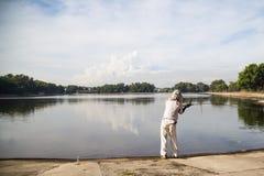 Wędkarza kasting przy spokojnym jeziorem Fotografia Royalty Free