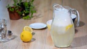 W dzbanku cytryny nalewa wodę Szkło iskrzastej wody napoju sodowana lemoniada z lodu i wapna cytryny plasterkiem na bielu zdjęcie wideo