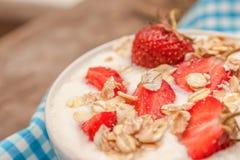 W filiżance jogurt, owsa granola i świeże truskawki na błękitnym, Obrazy Stock