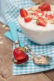 W filiżance jogurt, owsa granola i świeże truskawki na błękitnym, Zdjęcia Stock