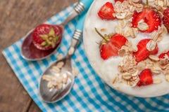 W filiżance jogurt, owsa granola i świeże truskawki na błękitnym, Zdjęcia Royalty Free