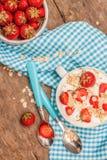 W filiżance jogurt, owsa granola i świeże truskawki na błękitnym, Zdjęcie Royalty Free