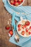 W filiżance jogurt, owsa granola i świeże truskawki na błękitnym, Fotografia Royalty Free