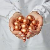 W górę dziewczyny ręki trzyma wiele barwionych złotych jajka przeciw tłu biały fartuch tła bogactwo burlap monet pojęcie bezpłatn zdjęcia stock