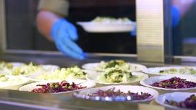 W górę, gablota wystawowa z sałatkami w bakłaszce, bałagan sala, bufet, Karmowy bufet resturant bufeta pracownik rozkłada jedzeni zbiory wideo