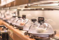 W górę Japońskiej konwejeru paska suszi restauracji na dokąd talerze z suszi umieszczają na płodozmiennym poręczu ochraniającym z zdjęcia stock