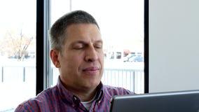 W górę klamerki przystojny w średnim wieku biznesowy mężczyzna w przypadkowych ubraniach używa cyfrowego pastylka przyrząd zbiory wideo
