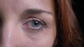 W górę portreta w średnim wieku brunetki caucasian kobieta ogląda poważnie w kamerę na czarnym tle zbiory