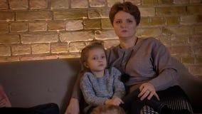 W górę portreta caucasian matka z córki dopatrywania filmem attentively i opowiadający z each inny w cosy domu zdjęcie wideo