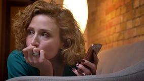 W górę portreta imbirowy z włosami dziewczyny lying on the beach na żołądku na kanapa zegarkach w smartphone zamyślenie na cosy d zbiory wideo