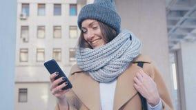 W górę portreta młoda atrakcyjna kobieta w eleganckim stroju Sprawdza Smartphone plenerowego przy miasta tłem zdjęcie wideo