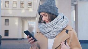 W górę portreta młoda atrakcyjna kobieta w eleganckim stroju Sprawdza Smartphone plenerowego przy miasta tłem zbiory wideo