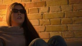 W górę portreta młoda caucasian dziewczyna ogląda horror na TV w 3D szkłach opiera na kanapie w strachu w cosy zdjęcie wideo