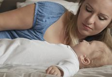 W górę portreta matka z jej dzieckiem na łóżku w sypialni Młoda atrakcyjna mama kocha jej syna szczęśliwa rodzina dzień macierzys zdjęcia stock