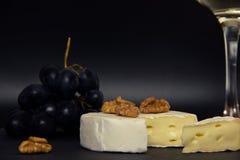W górę siekającego camembert sera, dokrętek i słodkich błękitnych winogron na tle szkło biały suchy wino, zdjęcie royalty free
