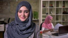 W górę ładnej twarzy muzułmańska kobieta w popielatym hijam jest przyglądający bezpośrednio przy kamerą podczas gdy być w ceglany