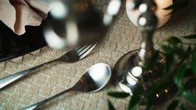 W górę łyżki i rozwidlenia lying on the beach na tablecloth na prawo od czarnego talerza krótkopędu przez candlestick zdjęcie wideo
