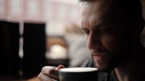 W górę atrakcyjnego mężczyzny pije kawę okno w kawiarni z szczecina zbiory wideo