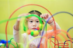 W górę Azjatyckiej dziecko dziewczyny bawić się edukacyjną zabawkę dla móżdżkowego rozwoju przy dzieciakami izbowymi obrazy stock