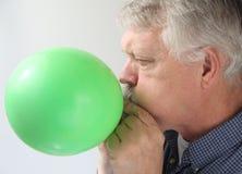 W górę balonu mężczyzna starszy dmuchanie - Obrazy Royalty Free