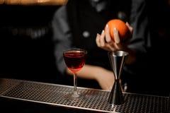 W górę barmanu trzyma koktajlu z osadzarki pozycją na baru kontuarze i pomarańcze zdjęcia stock