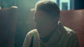 W górę blondynki facet z kolczykiem w ucho exhales gęstego dym w zwolnionym tempie zbiory wideo
