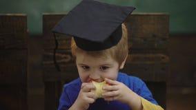W górę chłopiec w skalowanie kapeluszu który je jabłka w klasie Szkolna przerwa Głodny dzieciaka łasowania jabłko w sala lekcyjne zbiory wideo