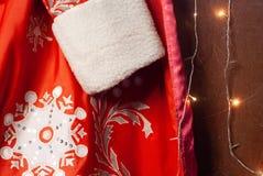 W górę czerwonego Święty Mikołaj futerkowego żakieta, Santa odzieżowego i girlandy, nowego roku tło, obrazy stock
