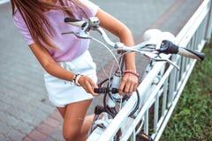 W górę, dziewczyna w lecie w mieście, stawia kędziorek na jej rowerze, ochrona przeciw kradzieży, rowerowy parking w mieście zako zdjęcia stock