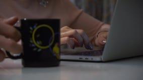 W górę dziewczyny wręcza pisać na maszynie na laptopie przy nocą Jej mąż przynosi ona kubek z herbatą lub kawą zdjęcie wideo