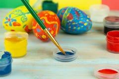 W górę farb i muśnięcia na multicolor drewnianym tle z Wielkanocnych jajek wielkanocy crufts zdjęcia royalty free