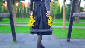 W górę huśtawki z żółtymi liśćmi wolno huśta się w parku na jesień dniu zbiory