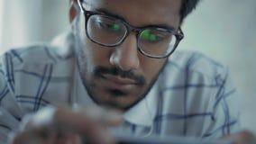 w górę, Indiański facet Słucha muzyka w hełmofonach na Smartphone z szkłami zdjęcie wideo