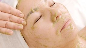 W górę kobiety z maską zielonych alg spirulina na jej twarzy Dziewczyna w piękno salonie bierze twarzowego Odmładzanie, fotografia stock