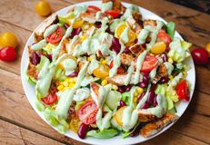 W górę kurczak sałatki z świeżymi warzywami w talerza i avocado opatrunku na drewnianym tle, obraz royalty free