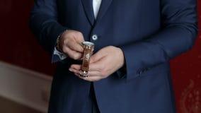 W górę mężczyzny w błękitnym kostiumu przymocowywa zegarek na jego ręce zbiory