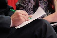 W górę mężczyzny ręki pisze na papierze z zielonym piórem Dorosła mężczyzn rejestrów informacja podczas spotkania w biurze obraz stock