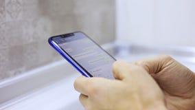 W górę męskich ręk trzyma smartphone, pisać na maszynie tekst na ekranie dotykowym Mężczyzny odpowiadania przyjaciela wiadomość w zbiory wideo