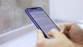 W górę męskich ręk trzyma smartphone, pisać na maszynie tekst na ekranie dotykowym Mężczyzny odpowiadania przyjaciela wiadomość w zbiory
