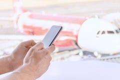 W g?r?, m?skie r?ki trzyma telefon kom?rkowego, lotniskowy rozmyty t?o fotografia royalty free